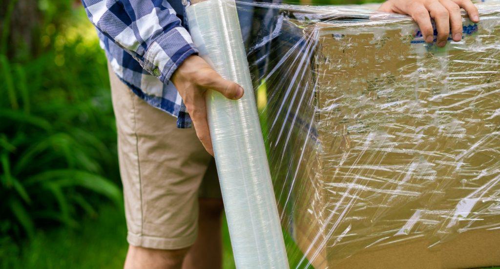 Homem embrulhando pacote com filme stretch
